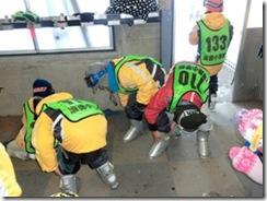 2.レッスン前。スキーブーツを履くのを手伝う子どもたち。